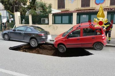 Auto in bilico sulla maxi voragine